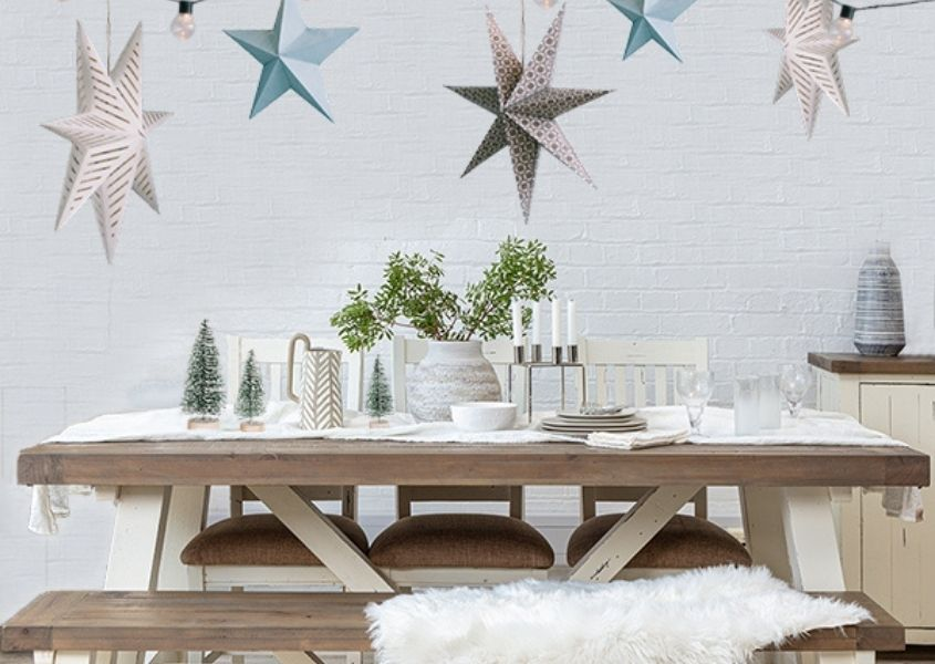 White reclaimed wood dining table with hanging christmas stars