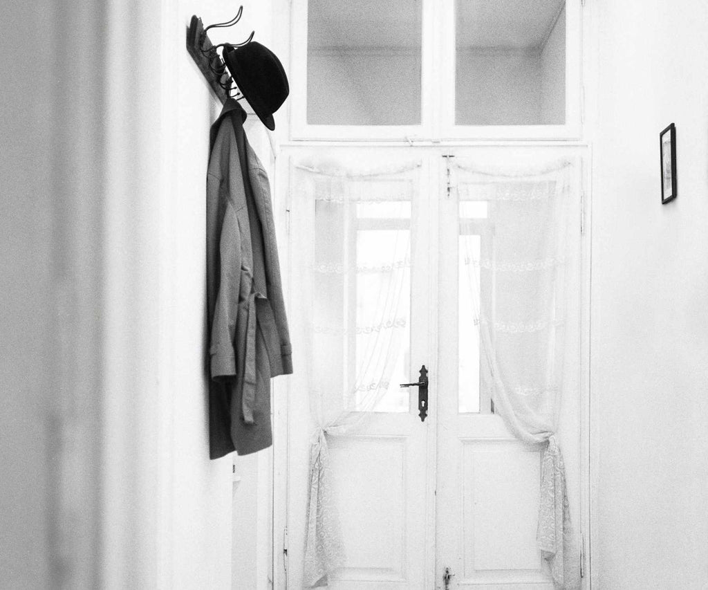 White hallway with grey coat and hat hanging on hooks