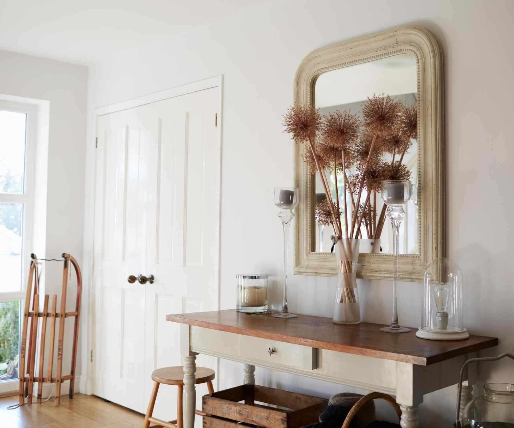 Bright hallway with wooden console table and mirror with dried flowers in vase