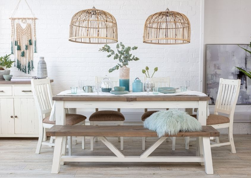 Double bamboo hanging pendant light over a reclaimed wood dining table with white painted legs and matching wooden bench