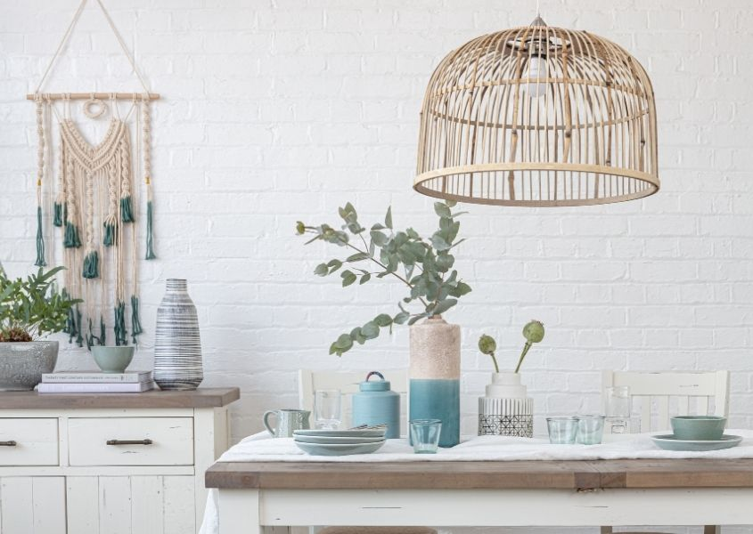 Bamboo hanging pendant light over white reclaimed wood dining table with vase and white table runner