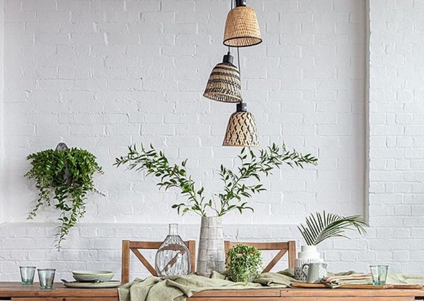 Three hanging bamboo pendant lights over dining table with green leaves in tall vase
