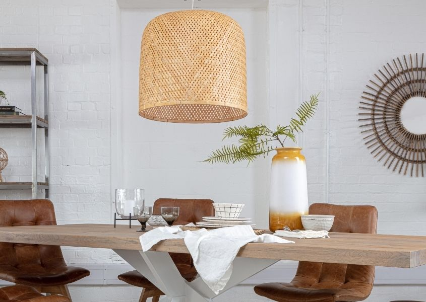 Large bamboo pendant light over large wooden dining table with white spider legs