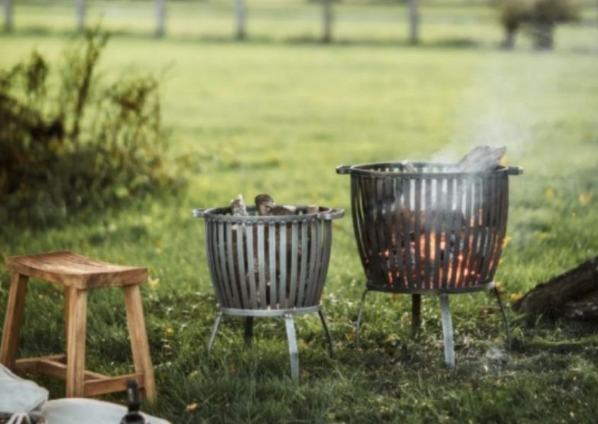 Two steel fire pits in a field with small wooden stool
