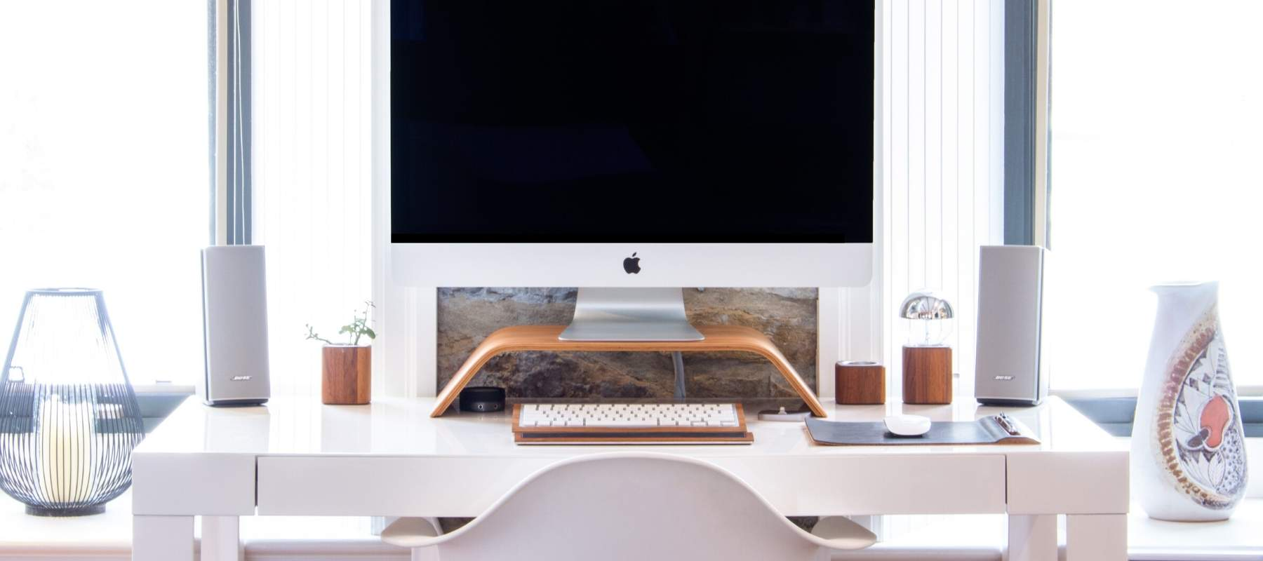 Mac on white desk in front of window