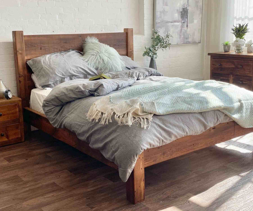 Reclaimed wood bed with grey bed covers and white cushions