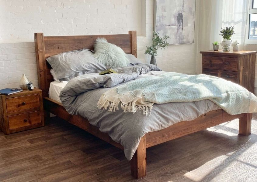 Reclaimed wood bed with light grey covers, blankets and cushions with small wooden bedside table