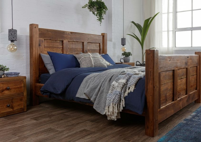 reclaimed wooden bed frame with blue covers and wooden bedside table