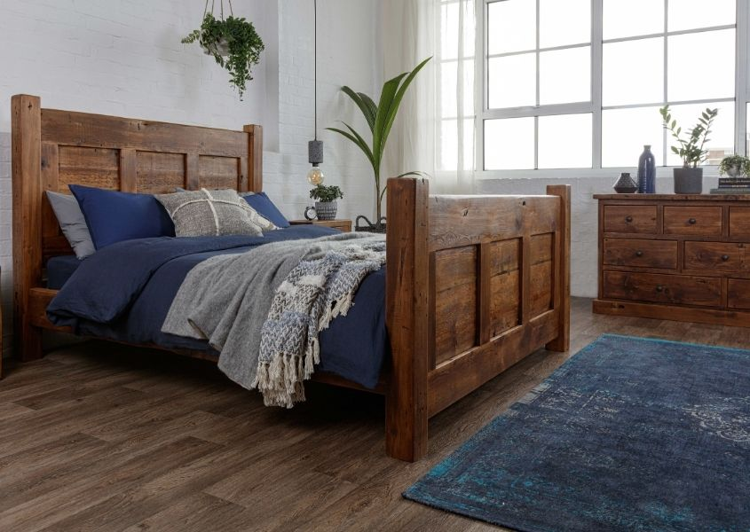 Reclaimed wood double bed with blue covers and blue floor rug