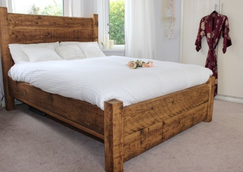 High back reclaimed wood bed with white covers and silk dressing gown hanging on white fitted wardrobes