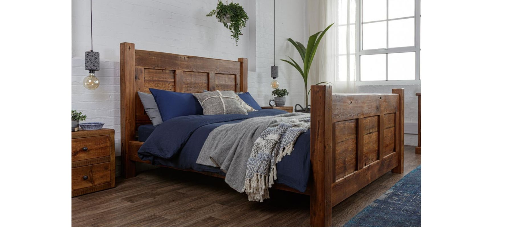 Reclaimed wood bed against white brick wall