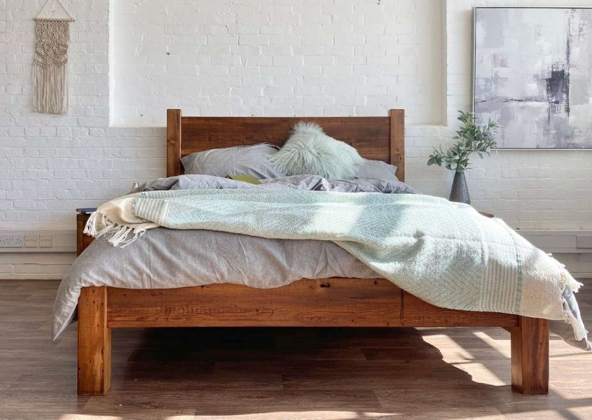 Reclaimed wood double bed with pale grey and green covers against a white brick wall with wall hanging