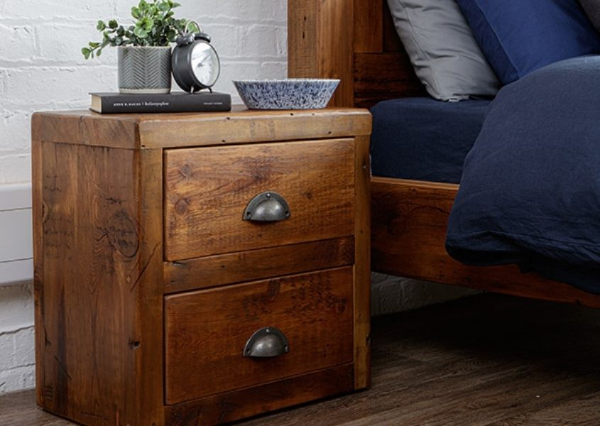 Reclaimed wood bedside table with two drawers and metal handle with small plant pot on top