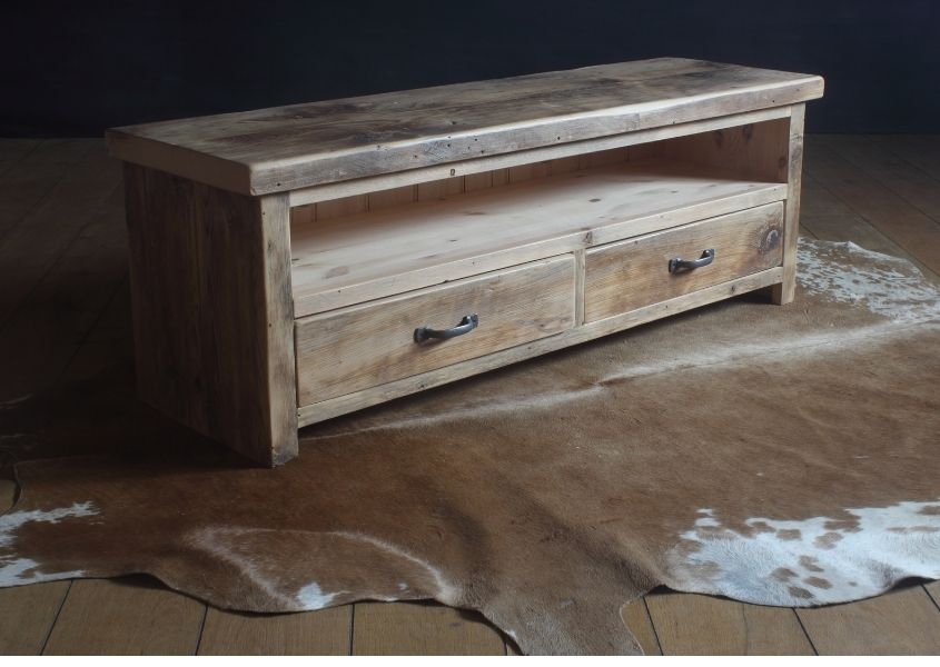 Reclaimed wood tv unit with two drawers on raw hide rug