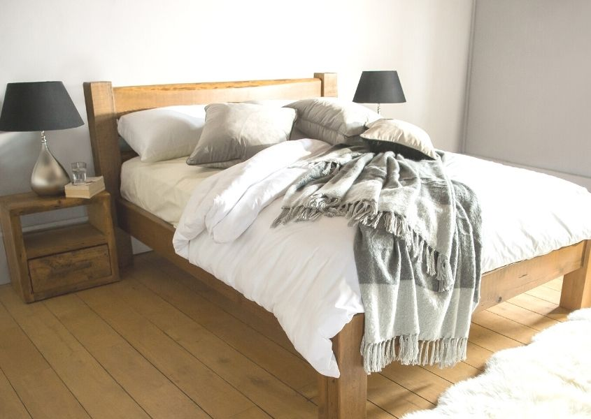Reclaimed wood bed frame with white covers and grey wool blanket thrown over bed
