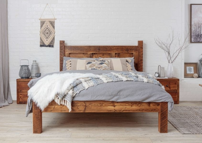 king size wooden bed frame with grey covers and matching wooden bedside tables