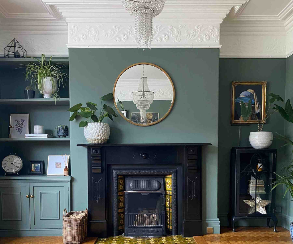 Victorian fireplace with dark grey walls and round wall mirror