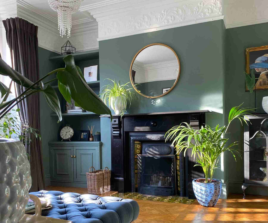 Dark living room with green plants and blue footstool