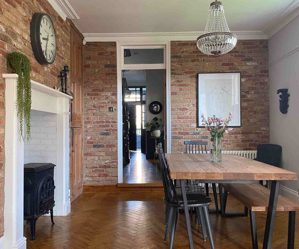 Dining area with industrial dining table, brick wall and white fireplace