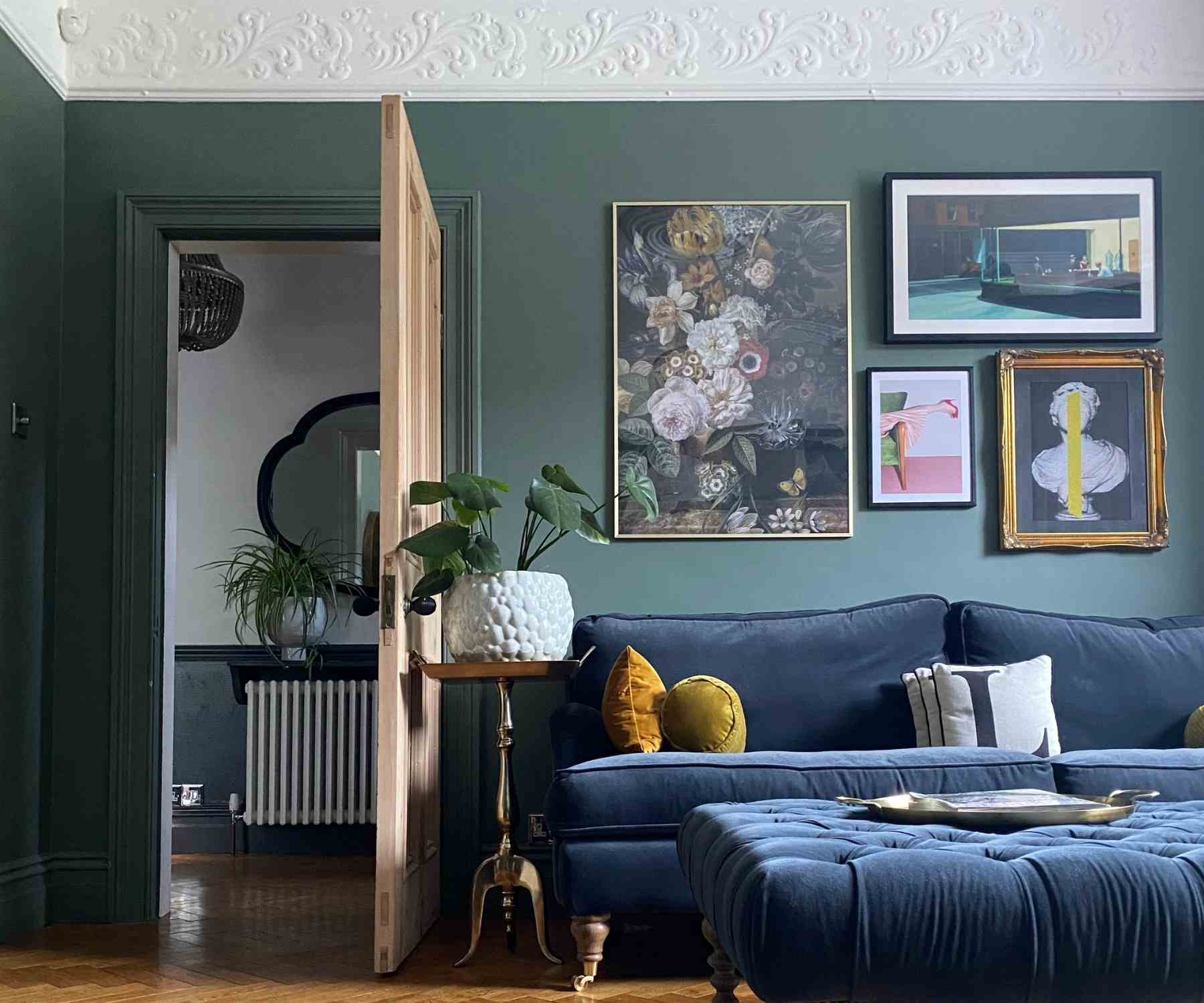 Living room with dark grey walls and deep blue velvet sofa