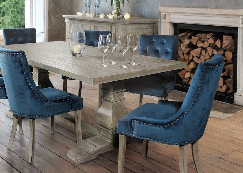 Reclaimed wood dining table with blue velvet dining chairs and set of wine glasses on tabletop