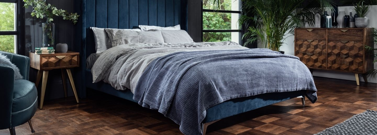 king blue velvet bed with large solid wood chest of drawers in mango wood
