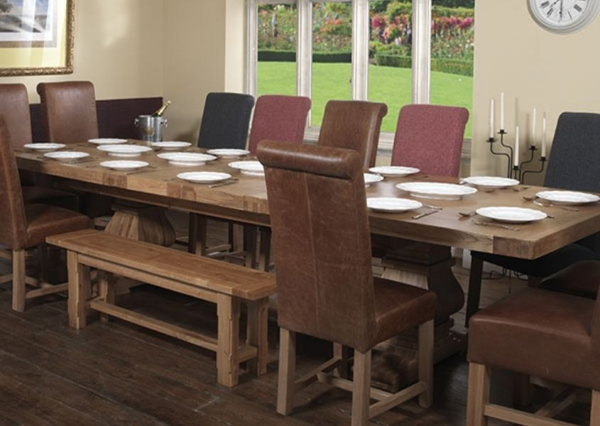 Large oak trestle dining table with high back brown leather chairs and wooden bench