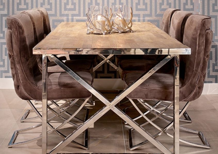 Velvet dining chairs around a silver framed reclaimed wood dining table
