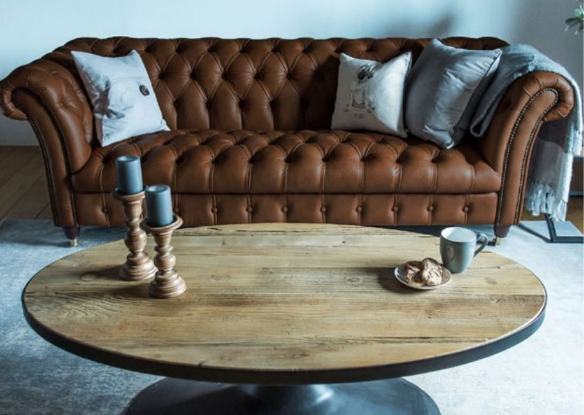 Tan leather chesterfield sofa with rustic round coffee table