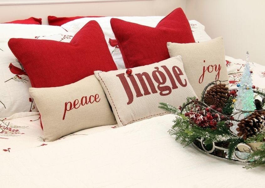 Christmas cushions on a white bed with pine cone Christmas display
