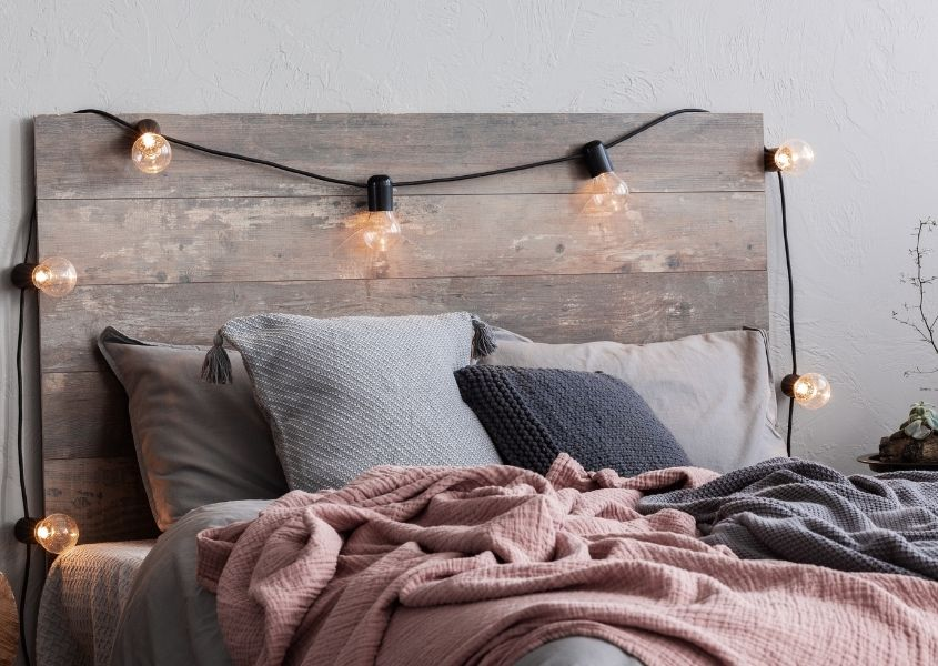 Wooden bed with fairy lights on headboard and scattered cushions