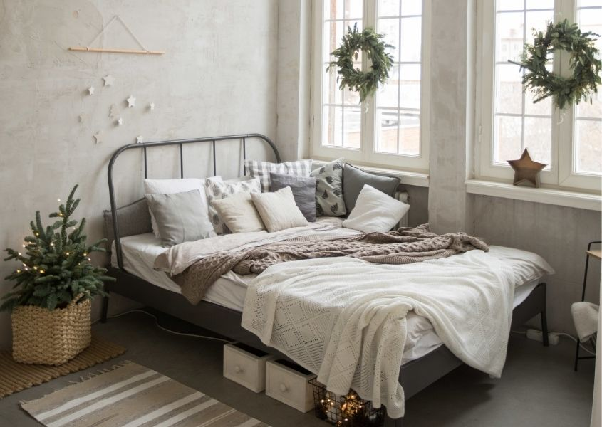 Metal double bed frame in bedroom decorated with hanging christmas wreaths on window and small Christmas tree