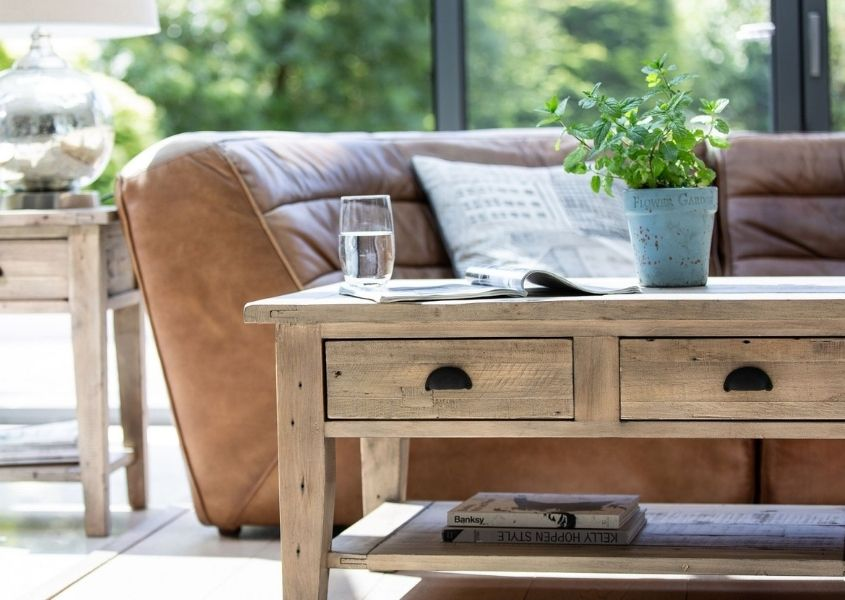Reclaimed wood coffee table with two drawer and brown leather sofa behind