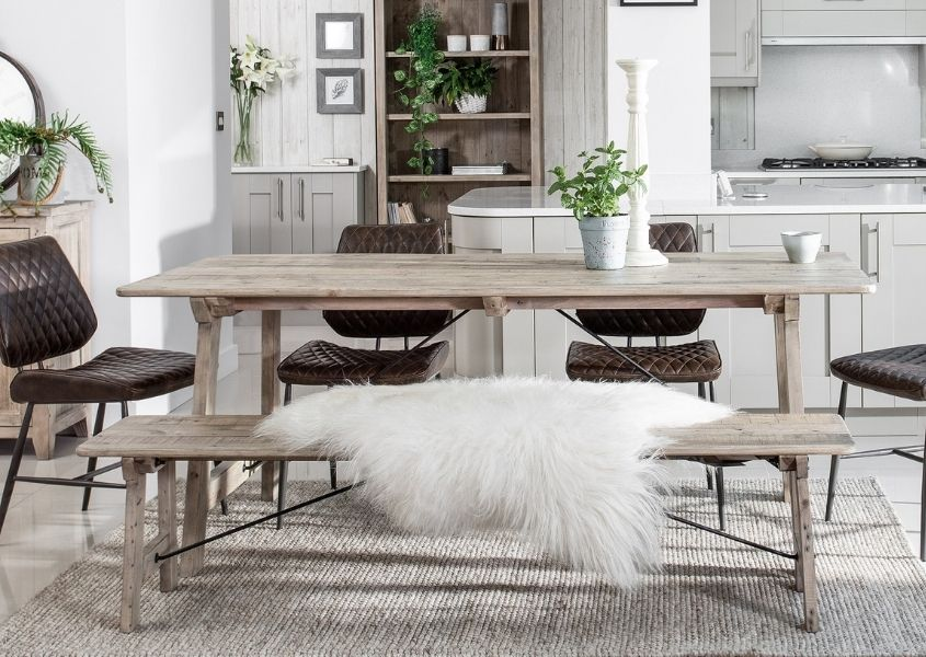 Rustic dining table with matching wooden bench with white faux fur throw and brown faux leather dining chairs