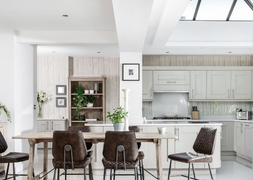 Pale reclaimed wood dining table in pale grey kitchen with brown leather dining chairs and large pitched roof skylight