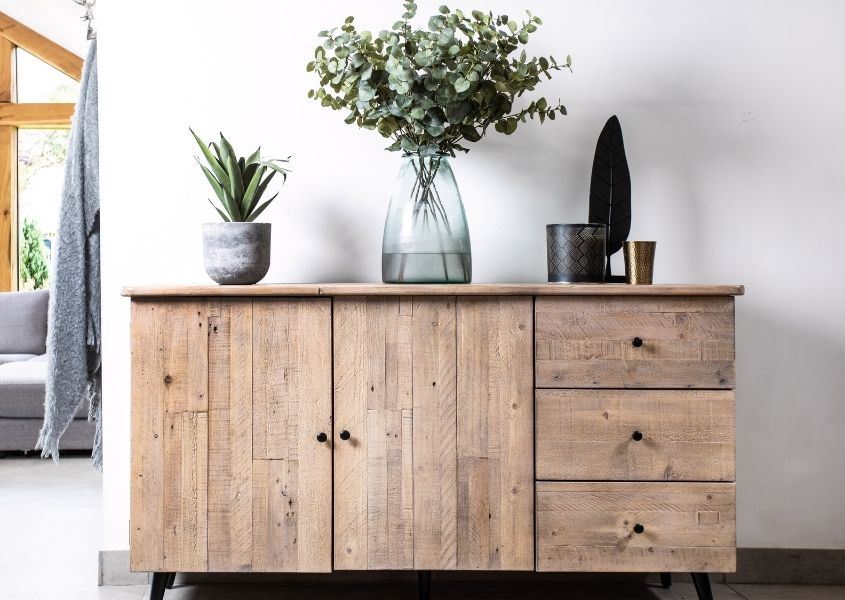 Reclaimed wood large sideboard with two cupboards and three drawers and large vase with eucalyptus leaves
