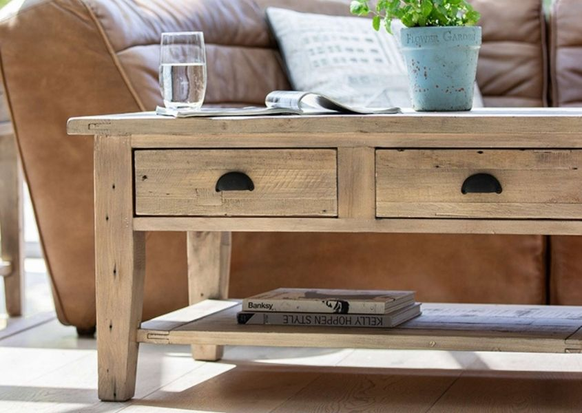 Reclaimed wood coffee table with two drawers and shelf and brown leather sofa behind