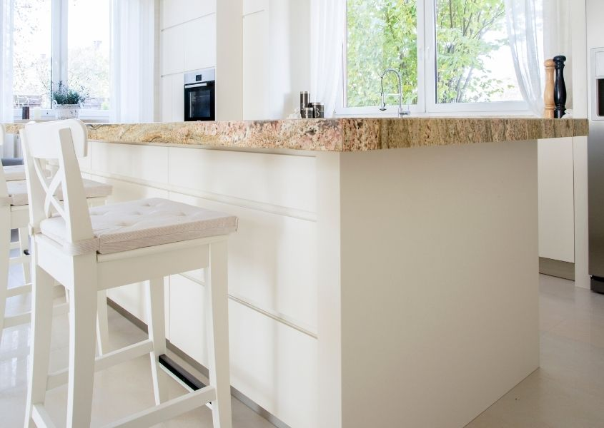 White wooden bar stool under white kitchen island with brown marble top