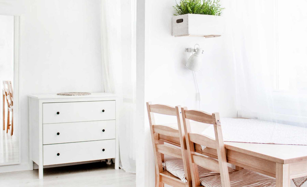 white desk with wooden chairs and white chest of drawers