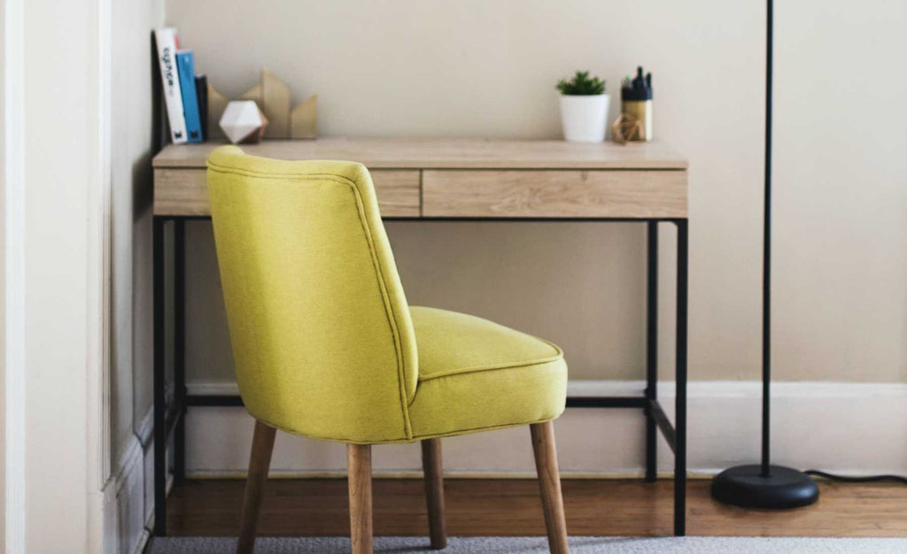 yellow fabric chair and wooden desk