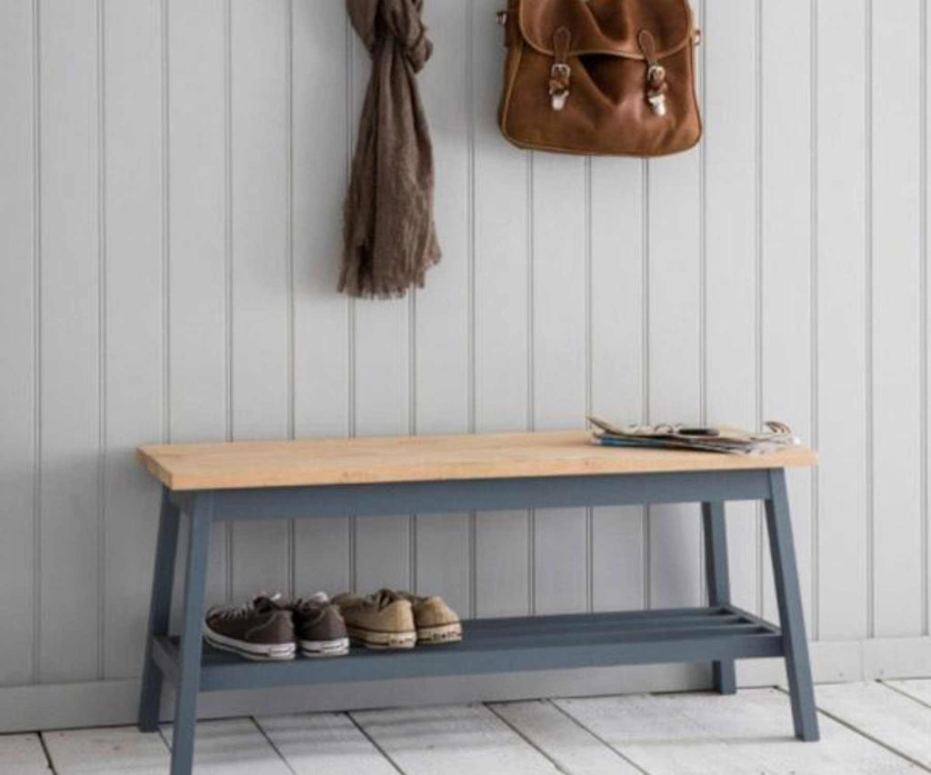 Wooden bench with blue legs against wood panelled wall