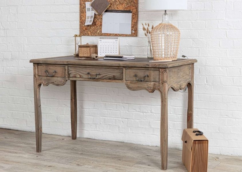 Reclaimed wood writing desk with glass table lamp and cork pin board on wall above
