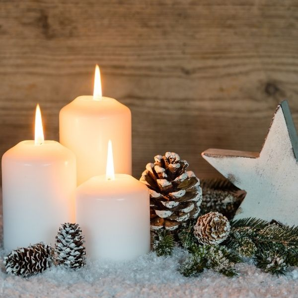 White lit Christmas candles with frosted pine cone against wood wall