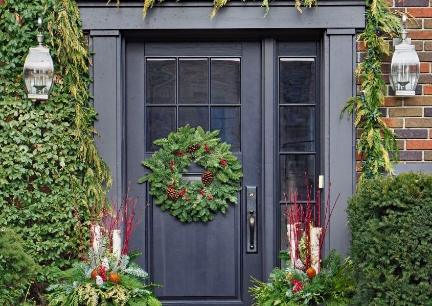 Dark blue front door with round green Christmas wreath and large green bushes