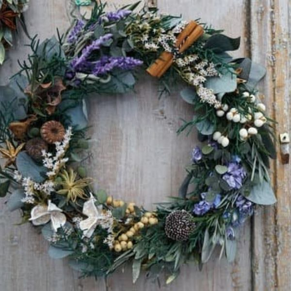 Rustic Christmas wreath with dried blue flowers, cinnamon stick and leaves