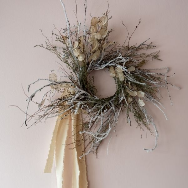 Modern wreath of long twigs and dried flowers with cream ribbon on neutral coloured wall