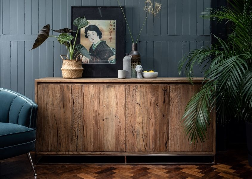 reclaimed wood sideboard with green palm and petrol blue velvet armchair