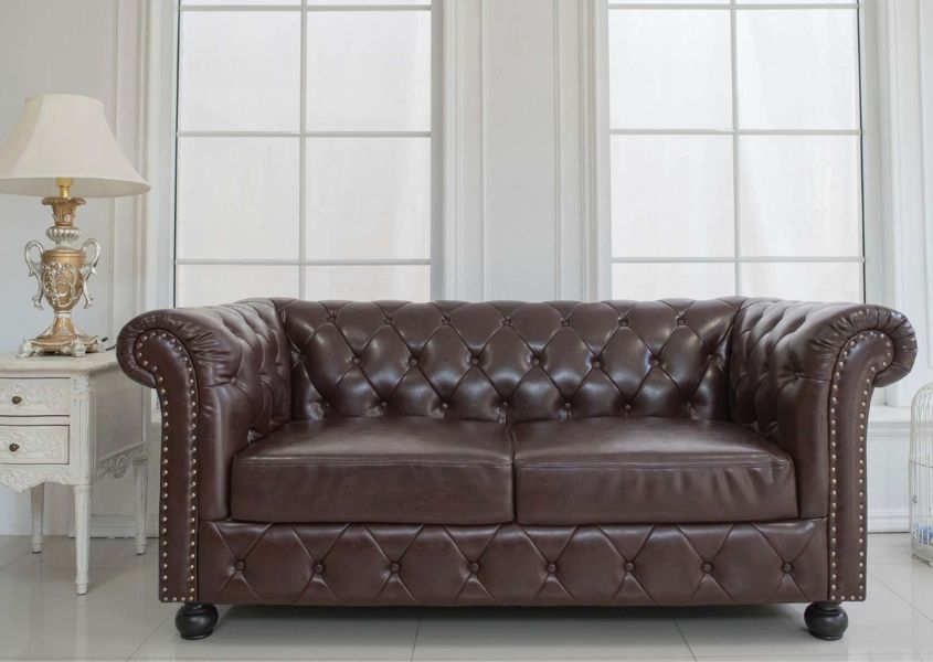 brown leather chesterfield sofa in white living room