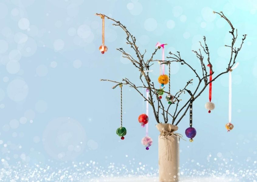Twigs in a vase with hanging Christmas decorations on a blue background