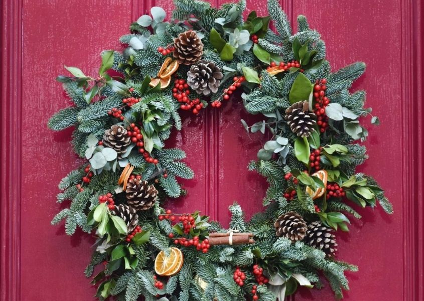 Christmas wreath made with pine leaves, cones & berries hanging on bright pink door